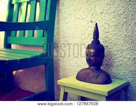 Buddha head garden ornament next to a green chair in evening light with a vintage filter