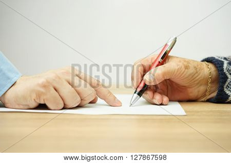 businessman man is pointing senior where to sign contract