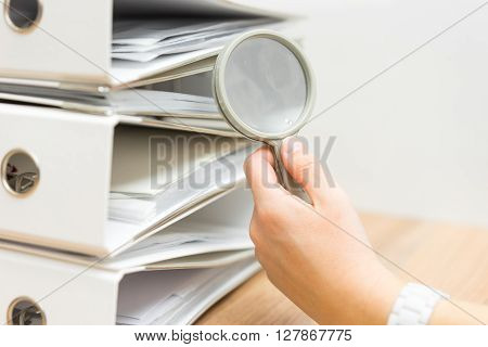 closeup of hand using of magnifying glass to inspect stack of documentation