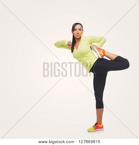 Beautiful sporty fit woman in sportwear making exercises. Isolated over white background. Copy space. Square composition.