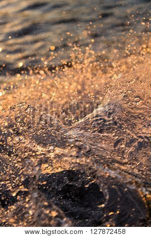 Water splash from motorboat at sunset in the Okavango Delta Botswana Africa. Warm colors from the setting sun.