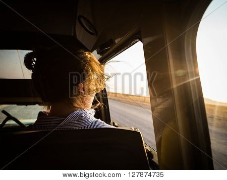 Girl on the road dreaming of a new beginning. Watching the sun setting over a memorable day.