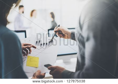 Business meeting image.Photo statistics document holding hand.Managers crew working with new startup project.Idea presentation, analyze marketing plans. Blurred background, film effect.