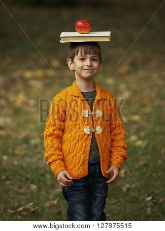 little funny boy with book and apple on his head
