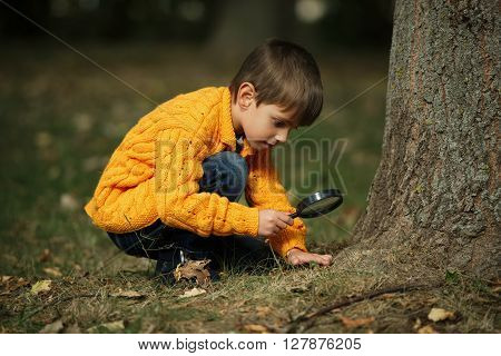 photo of little happy boy with magnifying glass
