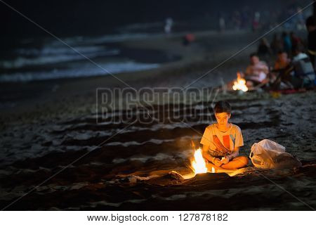 Mijas, Spain - June 23, 2015: Boy kindles a fire during Sant Joan holiday. It is one of the most important holiday in Spain. The fire is the symbol of the festival.