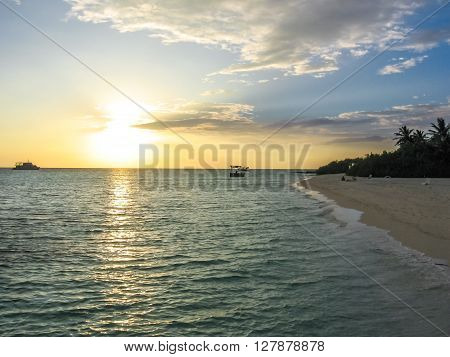 Sunset over the tropical sea and coral beach with colorful clouds in the sky. Boats on the horizon. North Male Atoll Asdu, Indian Ocean.