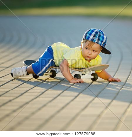photo of cute little boy with skateboard outdoors