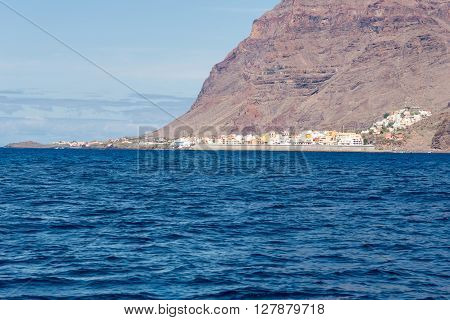 View from the atlantic to the island La Gomera. The steep coast on the west side with the Valle Gran Rey and the village Vueltas with harbor and seawall. On the hillside, the village La Calera