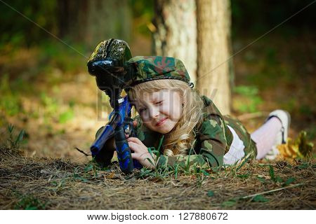 little girl in camouflage suit with rifle