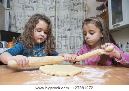 Two Girls Rolling Out Dough On Kitchen Table