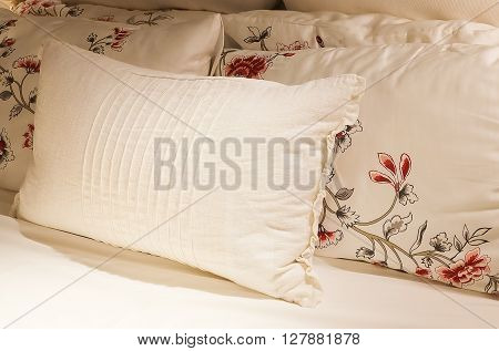 Luxury White Cozy Bed with Comfortable Soft Vintage Pillows in The Evening Time.