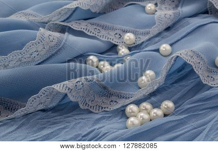 White pearls scattered on blue chiffon and lace background