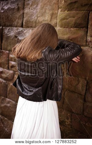 Back Of A Teenage Girl Leaning Against A Wall With Her Head In Her Hands