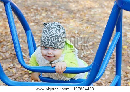 Little cute girl in vest climbs on blue ladder on playground at sunny fall day
