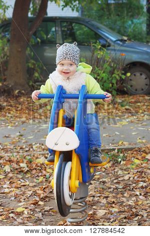 Little smiling girl in vest sits on wooden motorbike on playground at sunny day
