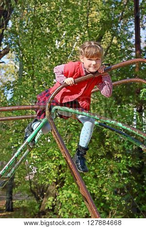Little girl climbs and smiles on playground in sunny autumn day