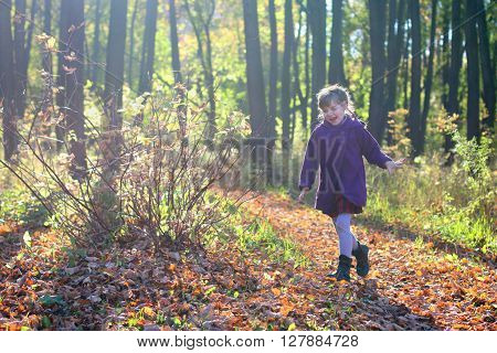 Little beautiful girl in coat runs in park in sunny autumn day