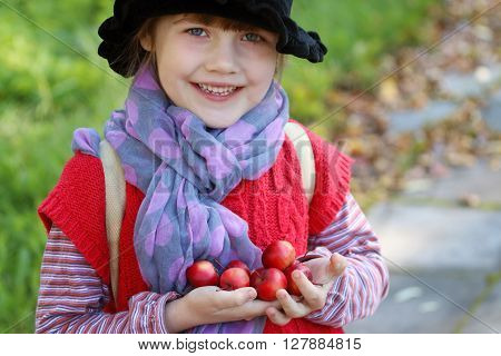 Little cute girl in black hat holds small red apples and smiles at autumn day