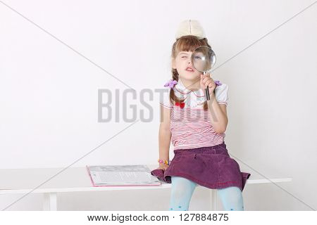 Little cute girl sits on bench with book and looks through magnifying glass