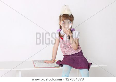 Little girl sits on bench with book and looks through magnifying glass