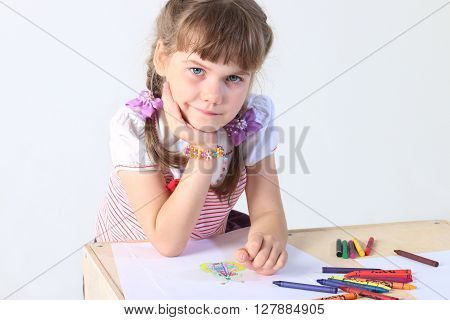 Portrait of little girl sits at table with paper sheets crayons in studio