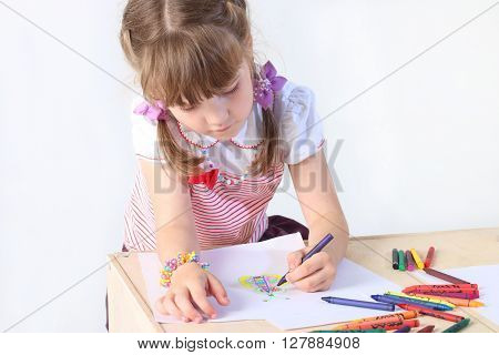 Portrait of little girl paint on paper sheets with crayons in studio