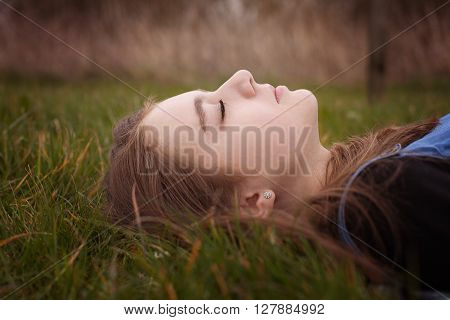 Pretty Teenage Girl Lying Down On Grass With Her Eyes Closed