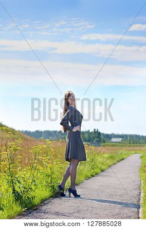 Young cute woman in dress poses on asphalt path at summer sunny day