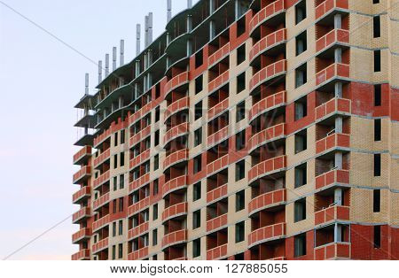 High brick residential building with skeleton of floors under construction
