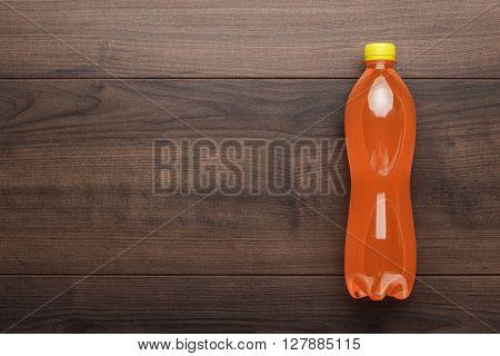 plastic bottle of orange soda on wooden table