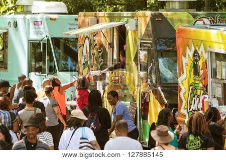ATLANTA, GA - APRIL 2016: A crowd of people buy meals from food trucks lined up in Grant Park at the Food-o-rama festival in Atlanta GA on April 16 2016 .
