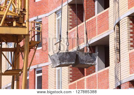 High residential building and hooks of crane lifting concrete solution on floor at construction site