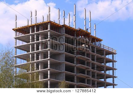 Big concrete residential building on construction site and pure blue sky with clouds