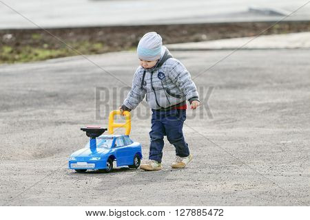 Handsome little boy in grey plays with toy car on asphalt outdoor at spring day