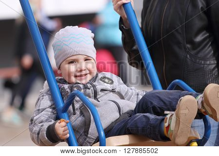 Happy little cute boy swings on playground and his mother hand at sunny spring day