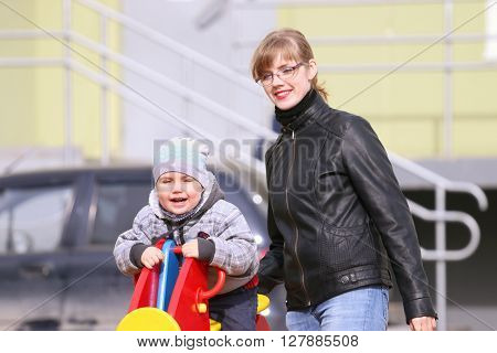Happy mother and her little cute son on playground at sunny spring day
