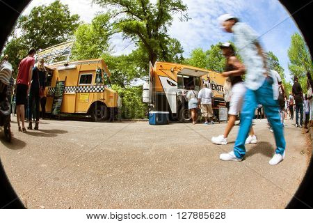 ATLANTA, GA - APRIL 2016: People motion blur in a circular fisheye scene as they walk past food trucks lined up in Grant Park at the Food-o-rama festival in Atlanta GA on April 16 2016 .