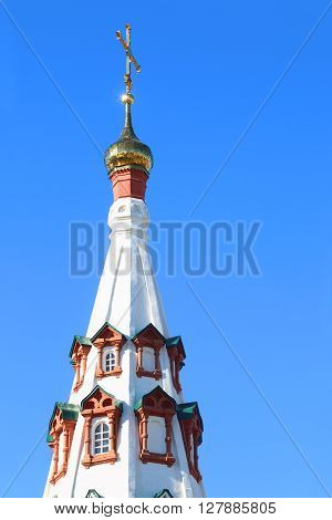 Golden small dome with cross of russian orthodox church at sunny day
