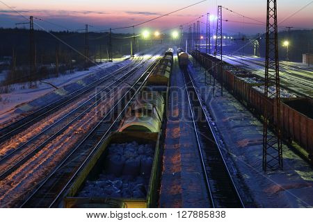 Top view of freight train with carriages on railways at winter night