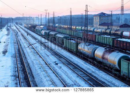 Freight train with tanks moves on railways at snowy winter evening
