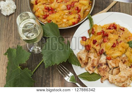 chicken with zucchini,zucchini stew with chicken,glass of wine and vine leaf