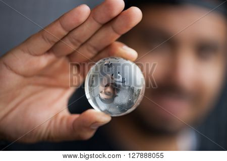 Young black man holding glass Earth model in hand. Concept for global connection ecology or planet care. Macro close up focus on globe