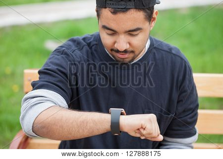 Smiling Young Black Man Using Smart Wrist Watches