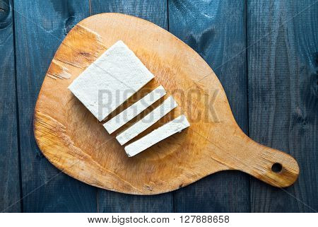 Slices of raw tofu on shabby wooden background. Top view
