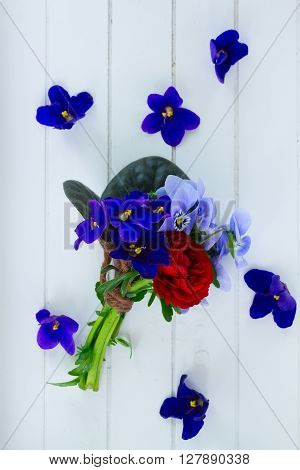 Posy of violets, pansies and ranunculus on white wooden background