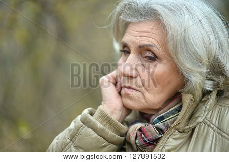 Nice sad old woman on the autumn background