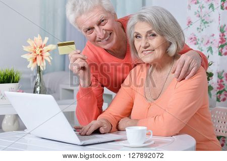 happy senior couple with laptop and credit card  at home
