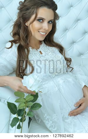fashion photo of beautiful pregnant woman with long dark hair posing in cozy interior with white rose