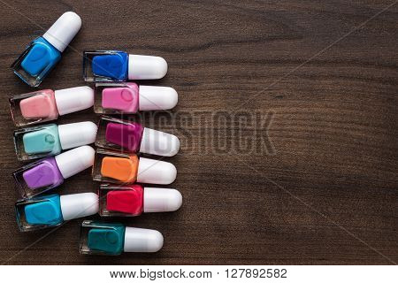 nail polish bottles of different colors on brown wooden table